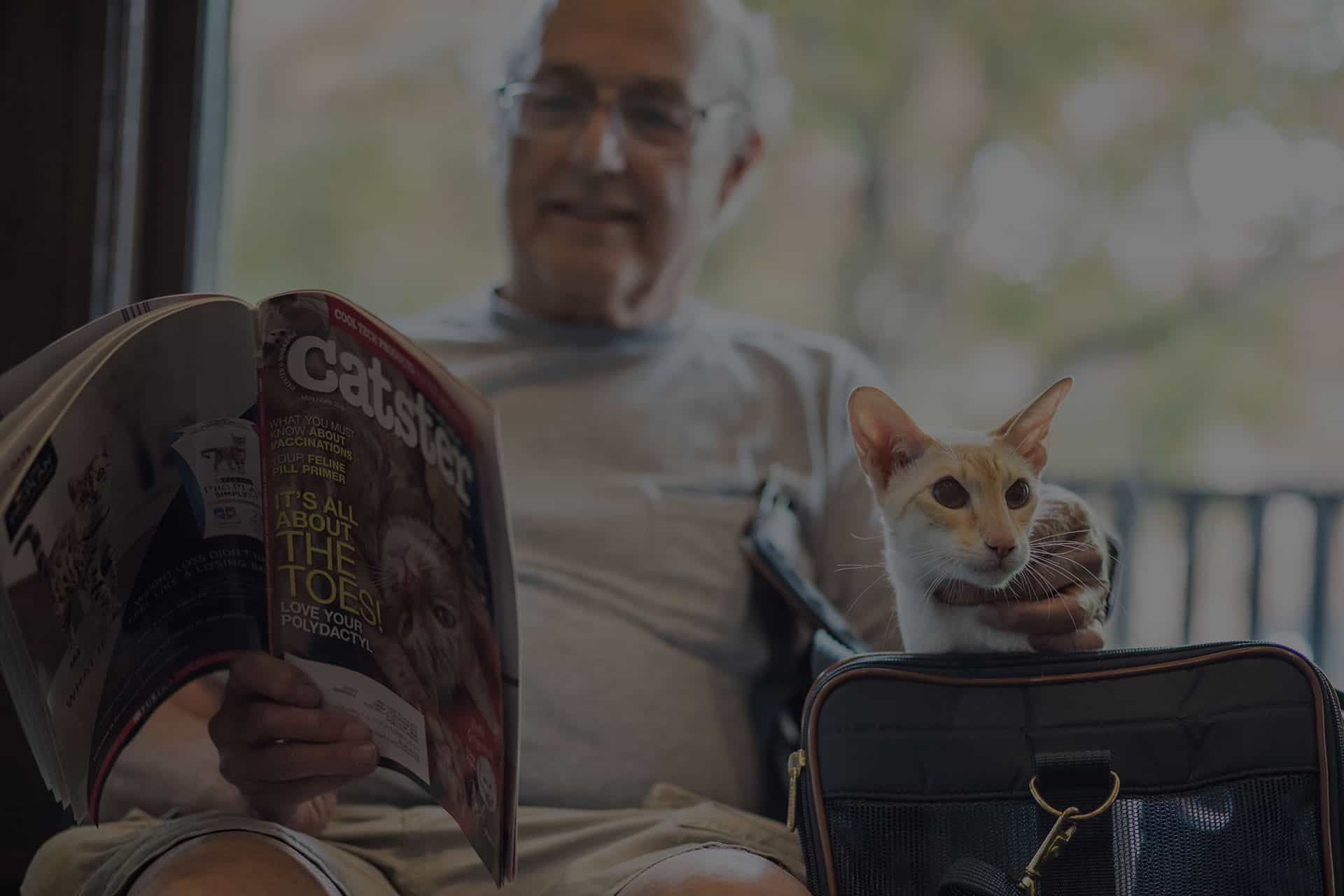 man reading magazine with his cat