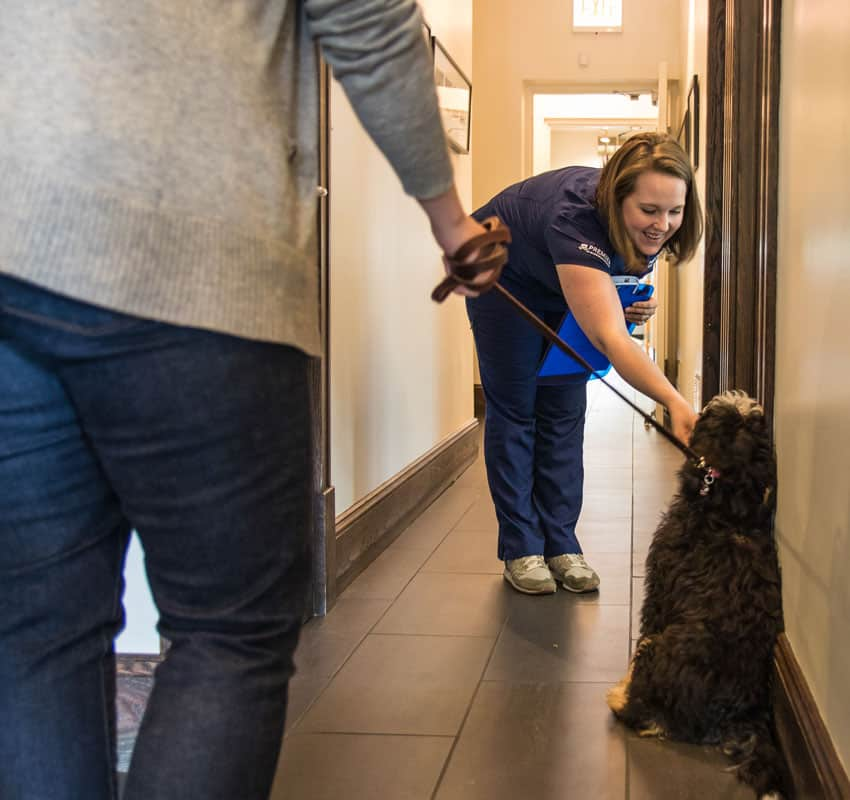Technician and dog in corridor